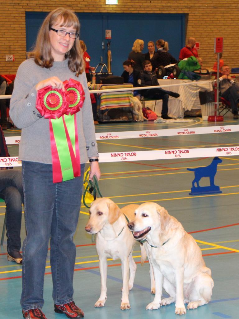 Anne Winkel modtager rosetter for at have opnået titlen Dansk Rallylydighedschampion for to hunde indenfor samme år. Til venstre er det DKRLCH Ravensbank FT (Pink) og til højre er det DKRLCH Melicmark Solar Energy.©Anne Winkel