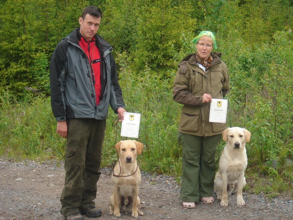 Two handlers and their dogs who have just qualified for participating in tests in Finland. To the right Mervi Salo with FI KVA, SE KVA Ravensbank Tip (Tipi), and to the left Ari Valto with Ravensbank Boss (Boss). ©Susanna Särkijärvi, Waterfowler Labradors